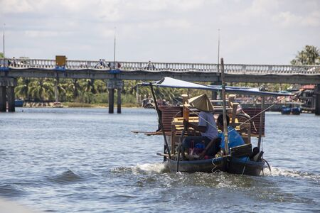 At Hoi An - Vietnam - On august 2019 - fisherman standing on a traditional boat floating on Thu Bon river