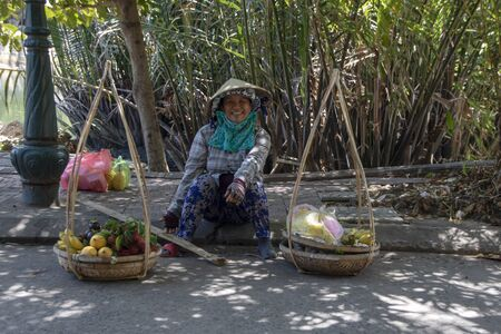 At Hoi An - Vietnam - On august 2019 - woman sitting with traditional weight for  goods