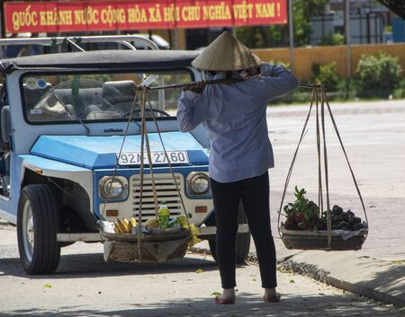 At Hoi An - Vietnam - On august 2019 - woman carrying goods on her  shoulder 新聞圖片