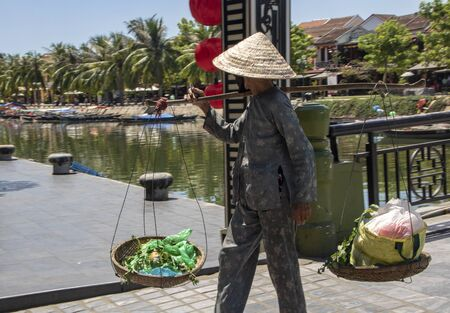 At Hoi An - Vietnam - On august 2019 - woman carrying  goods on her shoulders