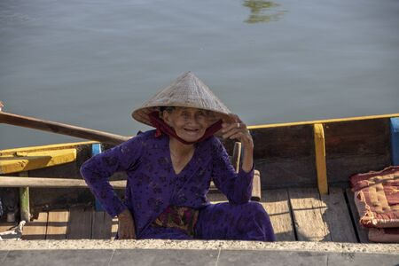 At Hoi An - Vietnam - On august 2019 - Old vietnamese woman sitting in a boat and smiling 新聞圖片