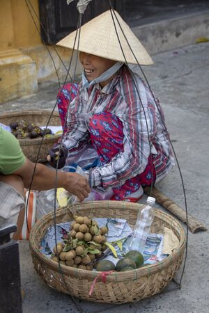 At Hoi An - Vietnam - On august 2019 - woman sitting with traditional weight for  goods 新聞圖片