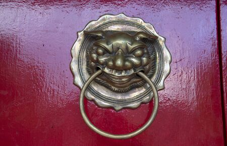 Bronze door knocker on the red door of Fukian Assembly Hall or Phuc Kien in the Hoi An ancient town in Quang Nam Province of Vietnam