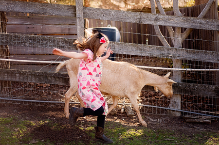 Little Girl Running with a Goat on a Farm