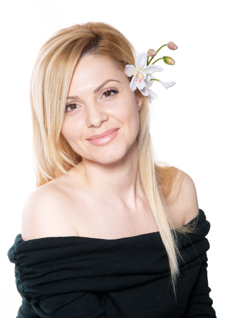 the blonde woman with long hair holding a flower orchid isolated on the white background Stock fotó