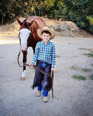 lead rope: Young boy dressed as Cowboy leading Paint Horse