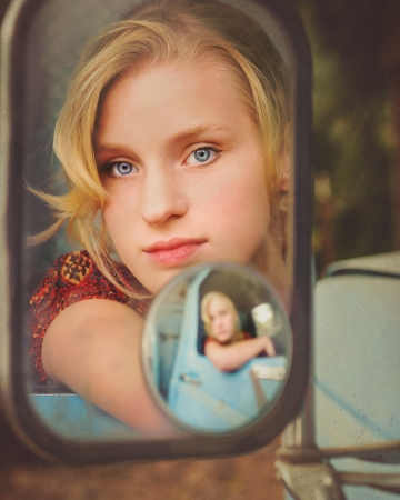 Girl looking in rearview mirror of old pickup truck Imagens