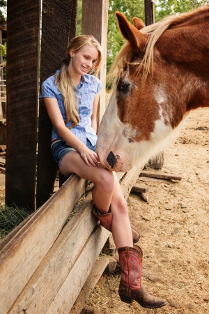 clydesdale: Young Girl sitting on a wood fence with Clydesdale
