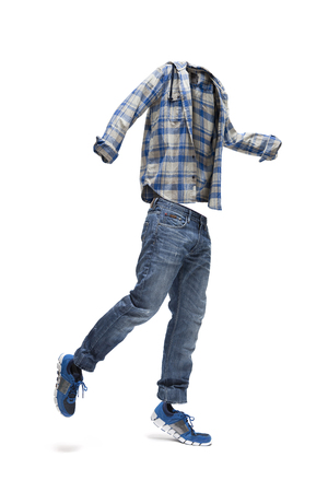 Jumping empty clothes. Checked shirt, worn jeans and blue trainers.