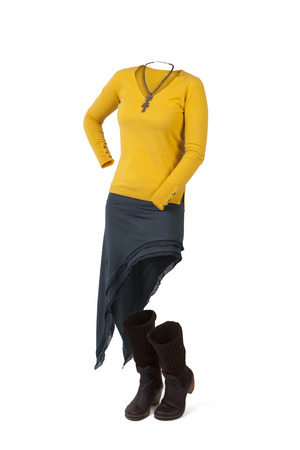 Empty clothes. Woman in smart casual clothes with yellow sweater, blue irregular skirt and brown boots.
