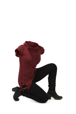Empty clothes. Woman down in her knees wearing red irregular t-shirt, black pants and boots.