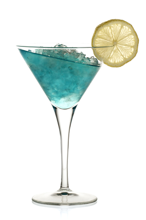 Blue alcoholic cocktail with leaning liquid and a lemon