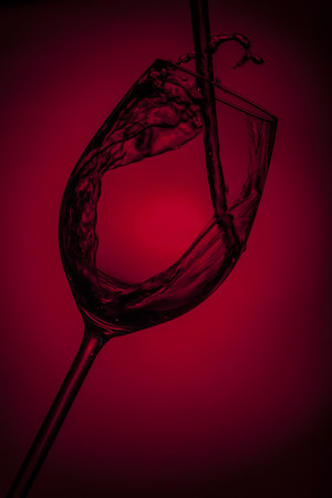 Red wine heavily poured in a glass in a red background Imagens