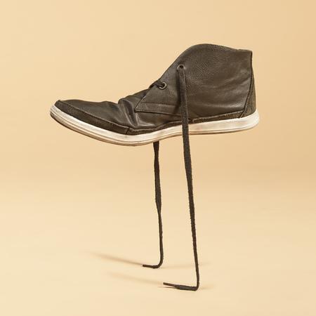 Grüner Schuh, der in seinen Schnürsenkeln steht. Konzeptfotomanipulation. Standard-Bild