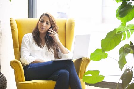 Young business woman having a call with a client in a hipster modern office.