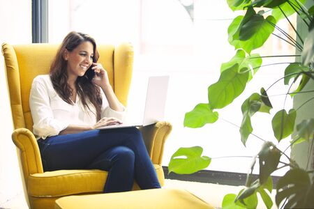 Cheerful freelancer designer making a telephone call to a client in a cool office space.