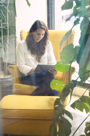 Startup founder studyng the first year results in a tablet device in her office couch.