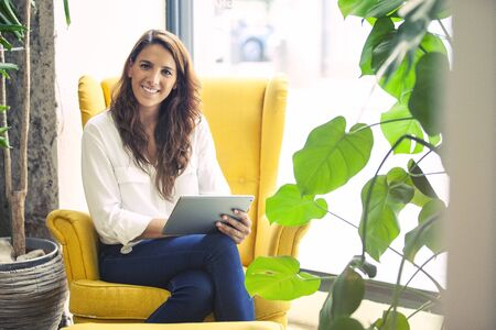 Portrait of a successful startup founder in the couch of her office, holding a tablet device.