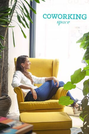 Member of a hipster coworking space having some rest in a yellow couch during her working hours.