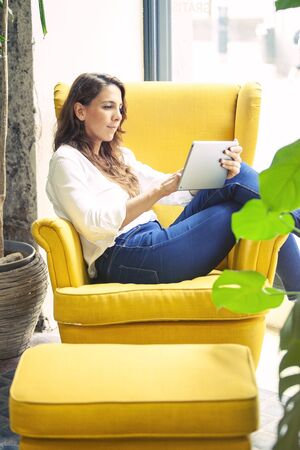 Young freelance designer working in a tablet device in the couch of her hipster coworking space. Imagens