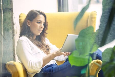 Young woman reading a book in a tablet device sitting in a yellow coach.