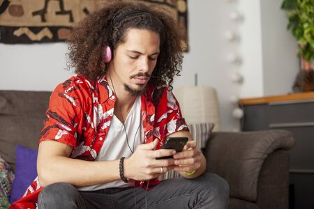 Young african american man choosing a song in his cellphone. Imagens