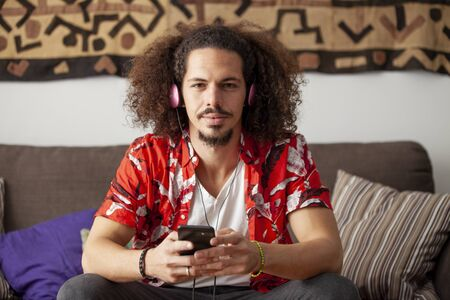 Young cuban man with afro hair listening music in his cellphone. Imagens - 135730921