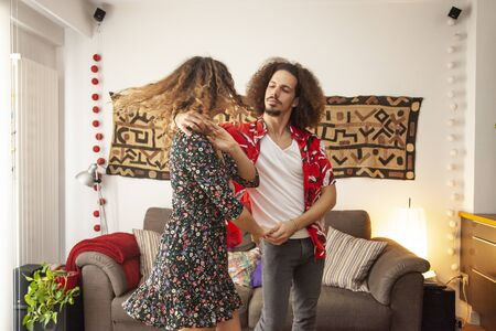 Lovely couple having fun dancing at home.