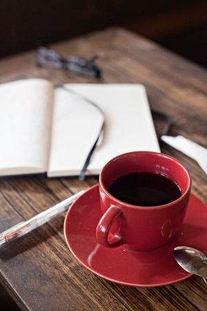 journals: Red cup and saucer with black coffee next to blank journal on wooden table Stock Photo