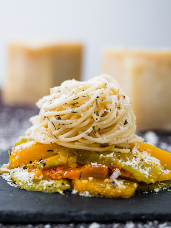 Spaghetti pasta dish with vegetables, herbs and cheese. Pieces of cheese visible on background. Banco de Imagens