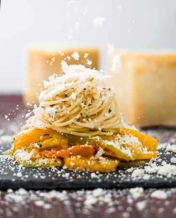 Falling cheese on a freshly prepared spaghetti pasta with vegetables. Fresh Piece of Cheese on background Banco de Imagens