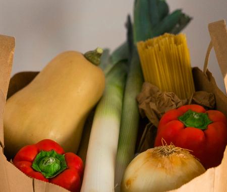 Paper shopping bag full of fresh vegetables and pasta.