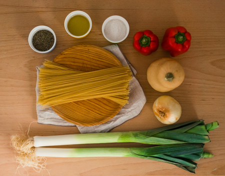 Fresh vegetables, pasta, olive oil and herbs on a wooden table. 版權商用圖片