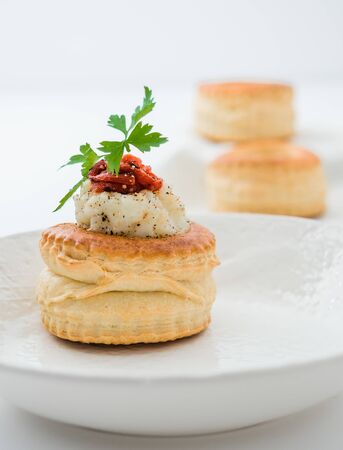 Canape vol-au-vents filled with potato salad and pepper on a white plate Stockfoto