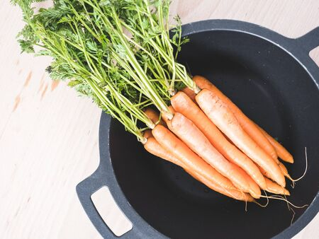 Bunch of organic carrots with leafs in a black wok Stockfoto