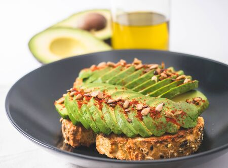 Sourdough toast with avocado and spanish paprika powder. Fresh avocado and olive oil in the background Фото со стока