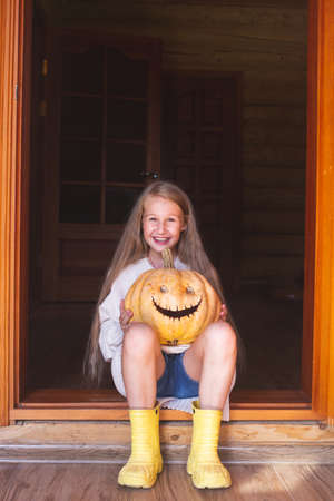 A beautiful cheerful girl with long hair is sitting on a doorstep, holding a orange pumpkin with eyes and mouth in her hands.Halloween, holiday.
