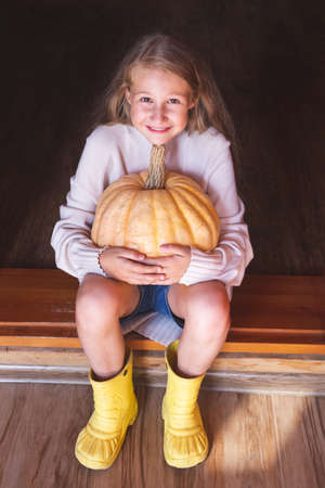 A beautiful cheerful Caucasian girl sits on the doorstep of the house, holding a large orange pumpkin in her hands. Halloween. Autumn harvest, farm.