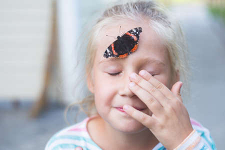 A beautiful black butterfly with orange spots, sits on a forehead of a blond Caucasian girl of 7-8 years, who covered her eyes with her hand.