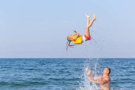 A man in sea tosses a 4-5 year girl.Child in a life jacket with splashes flies upward, does a somersault, trick against background of blue sky and sea