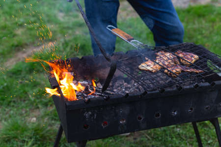 Meat is grilled. A man stirring coals with a hot poker. Sparks fly from fire in grill. Outdoor cooking. Picnic, weekend