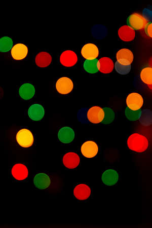 Multicolored bokeh from garlands on a black background. A versatile festive and magical backdrop.