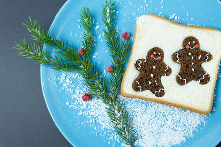 Bread toast, gingerbread men, spruce branch on a blue plate. Christmas, new year. Festive breakfast, creative food.