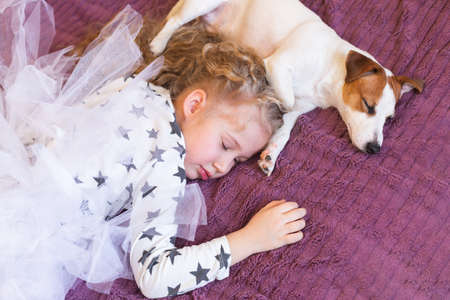 Little blonde girl in pajamas with stars and a dog Jack Russell Terrier sleep together on a purple plaid. Daytime sleep