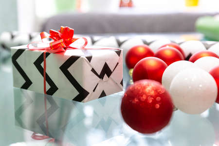 Red and white Christmas balls are scattered on the glass table. Christmas gift, wrapping paper, red bow. New Year, xmas.