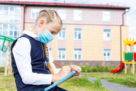 A girl in a blue school uniform and a medical mask sits and writes with a pen in a notebook outdoors against background of school building and playground. New school year, new normal. Copy space