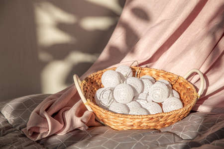 Garland of white balls in a wicker rattan basket on the bed. Textile pink and gray background.Christmas, new year. Home decor, comfort. Still life in beautiful delicate shades. Light and shadow. 版權商用圖片