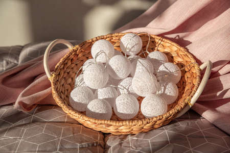 Garland of white balls in a wicker rattan basket on the bed. Textile pink and gray background.Christmas, new year. Home decor, comfort. Still life in beautiful delicate shades. Light and shadow.