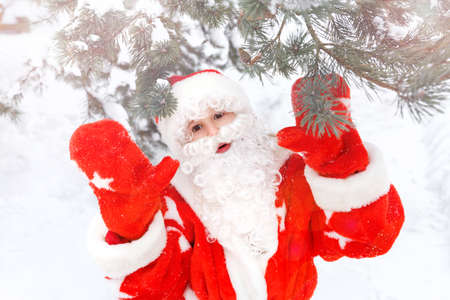 A child in a red santa claus costume in a winter forest shows hands in mittens, looks at camera. Christmas, new year, winter.