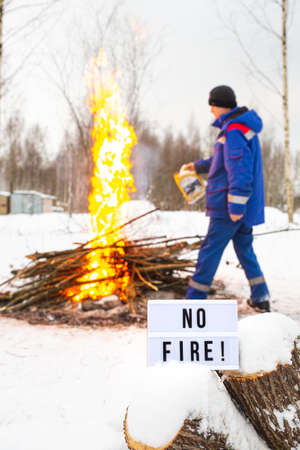 A man in a blue uniform pours gasoline from a canister into the fire. Open fire warning. A sign with the text No fire.